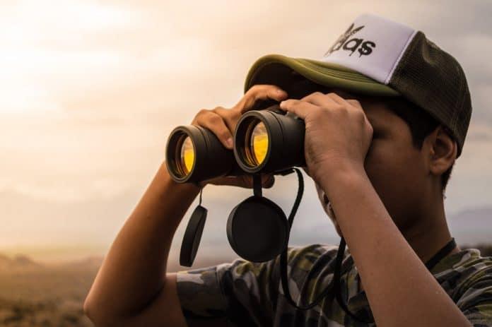Young man using black binoculars